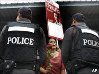 A supporter of detained red-shirt leader Kokaew Pikulthong faces police outside Bangkok district office on 28 June 2010