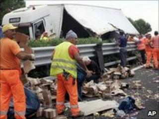 Workers collect euro coins after the lorry accident near Foggia