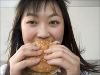A woman eats a hamburger (file photo)