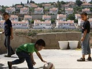 Palestinian boys in the West Bank with the Jewish settlement of Halamish in the distance