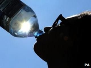 Woman drinking water in the sunshine