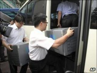 South Korean prosecutors carry boxes from the raided prime minister's office in Seoul on 9/7/2010