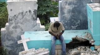 A man prays in a cemetery affected by the 12 January earthquake in Port-au-Prince on 10 July 2010