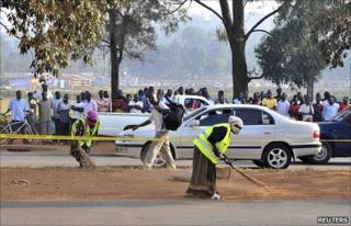 People gather across a street at one of the scenes of Sunday's bomb blasts in Kampala