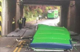 The bus roof lying in the road below the bridge