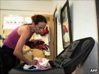 Irene Viera, the wife of community organiser Julio Cesar Galvez, packs a suitcase (12 July 2010)