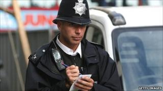 Policeman writing in notebook