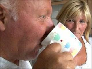 Derek Webster drinks a cup of tea as his wife Shirley looks on