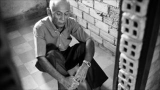 Chum Mey poses for photo at his former cell in the Tuol Sleng prison (July 2010)
