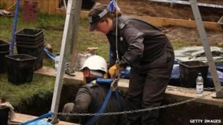 Police officers examining a well in the garden of a property in Portslade