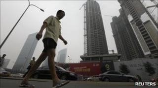 Man walks past tall buildings in China