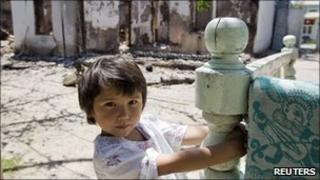 An Uzbek girl in front of her house, burned down during ethnic clashes in Osh in June
