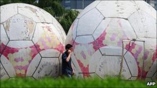 A man walks past giant footballs in Beijing, China (23/06/2010)