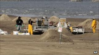 Workers cleaning up the beach on Grand Isle, Louisiana, on 16 July