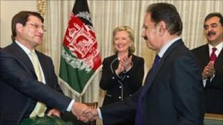 Afghan Trade Minister Anwar Ul Haq Ahadi (left) sakes hands with his Pakistani counterpart Makdoom Admin Fahin as US Secretary of State Hillary Clinton looks on in Islamabad. Photo: 18 July 2010