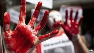 Demonstrators display fake blood on their hands and a poster of Rwanda's President Paul Kagame during a protest against his presence in Madrid on Friday 16 July 2010