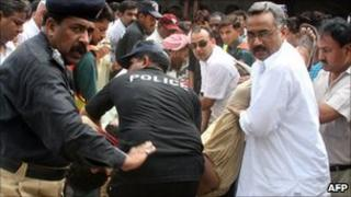 Security officials carry the bodies of two Christians killed outside a court in Faisalabad on 19 July 2010