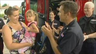 Amber is congratulated by firemen