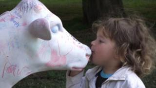 Child kissing model cow