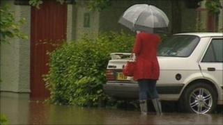 Woman holding umbrella wading through floods in Perth