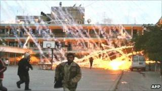 Palestinians running for safety as white phosphorus lands on a UN-run school in Beit Lahia (file photo 17 January 2009)