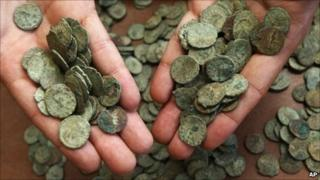 A British Museum staff member displays handfuls of the coins
