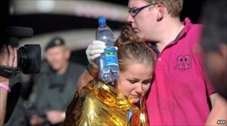 A man comforts a woman at the Duisburg music festival
