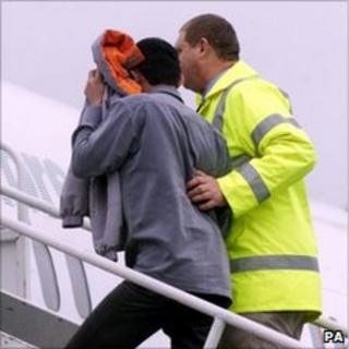 A failed asylum seeker being escorted onto a plane for removal from the UK
