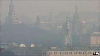 The spires of the Kremlin and St Basil's cathedral are seen through smog in Moscow