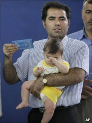An Iranian man uses his identification card to fan air over the baby he is holding, as he waits in line to cast his vote in the presidential elections, 2009.