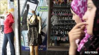 Women walk past mannequins in Gaza city 28 July 2010