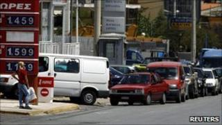 Cars line up at a petrol station in Athens on 28 July 2010