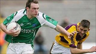 Peter Sherry of Fermanagh fends off the challenge of Wexford's Adrian Flynn