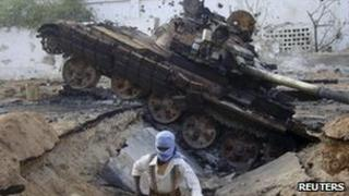 Al-Shabab fighter next to destroyed AU tank