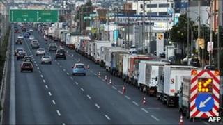Trucks left by striking truckers stand on the Athens-Thessaloniki national road on July 29, 2010