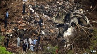 Investigators search amid plane wreckage in the Margalla hills on the outskirts of Islamabad, Pakistan, 31 July 2010