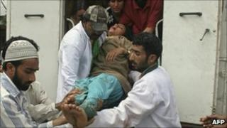 Relatives and paramedics carry an injured Kashmiri woman outside a hospital in Srinagar on 31 July 2010