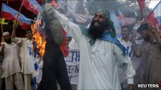 Supporters of Shabab-e-Milli burn an effigy of David Cameron in Karachi 31 July 2010