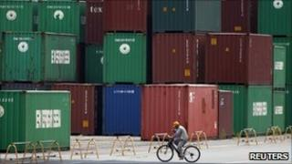 A worker rides a bicycle past stacked cargo containers at a port