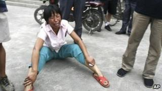 A woman cries after a tractor went on the rampage in Hebei province in China 1 August 2010