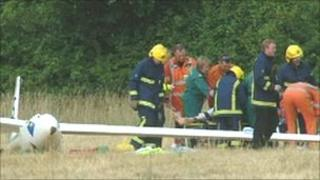 Emergency crews tend to the injured pilot