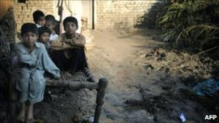 Flood survivors sit on a wooden bed outside their destroyed house in Charsadda