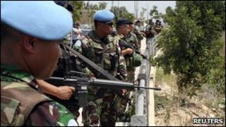 Lebanese soldiers and U.N. peacekeepers stand at the Lebanese-Israeli border