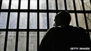 A prisoner staring through bars in an English jail
