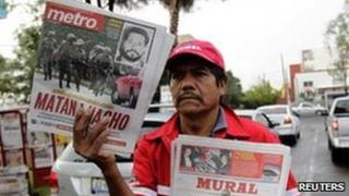 """A newspaper vendor holds local newspapers with front page stories about the death of Ignacio """"Nacho"""" Coronel, a major Mexican drug trafficker, in Guadalajara 30 July 2010."""