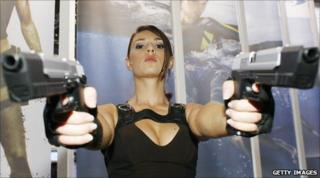 An actress dressed-up as Lara Croft from Tomb Raider poses for a photo