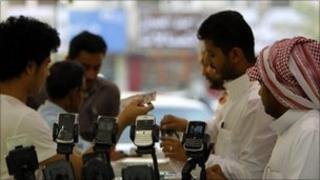 Men stand near Blackberry phones on sale at a shopping mall in Riyadh - 5 August 2010