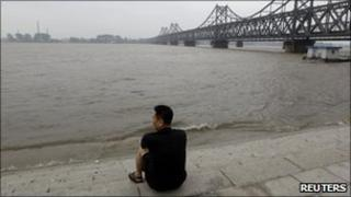 A Chinese resident looks at the rising water level of Yalu River opposite the North Korean town of Sinuiju