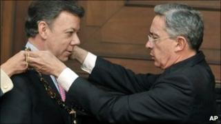 President Alvaro Uribe, right, decorates Colombia's President-elect Juan Manuel Santos with the National Merit Order
