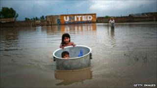 A girl floats her brother across floodwaters in Sukkur (7 August 2010)